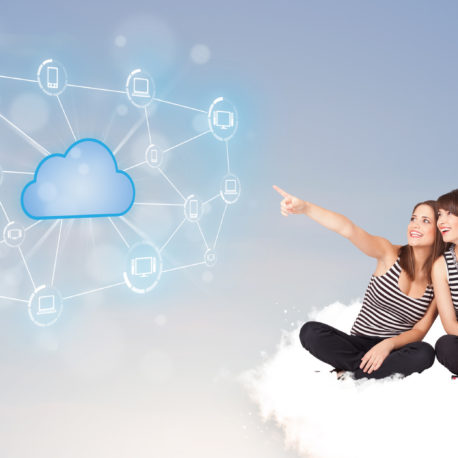 Happy young women sitting on clous with cloud computing